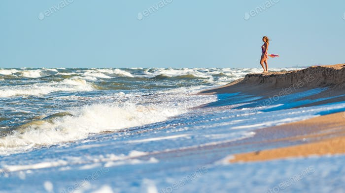 Joyful young woman enjoys stormy waves on sea shore