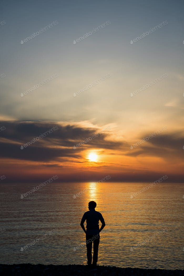 Young man standing at the beach in front of amazing sea view at sunset or sunrise and thinking about