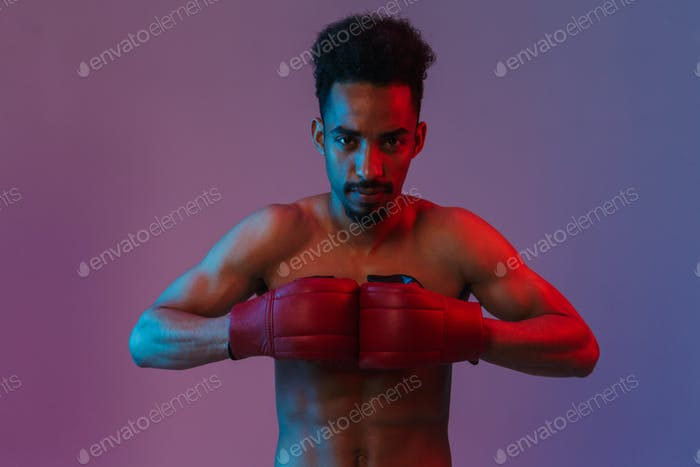 Portrait of masculine shirtless african american sportsman poising in boxing gloves