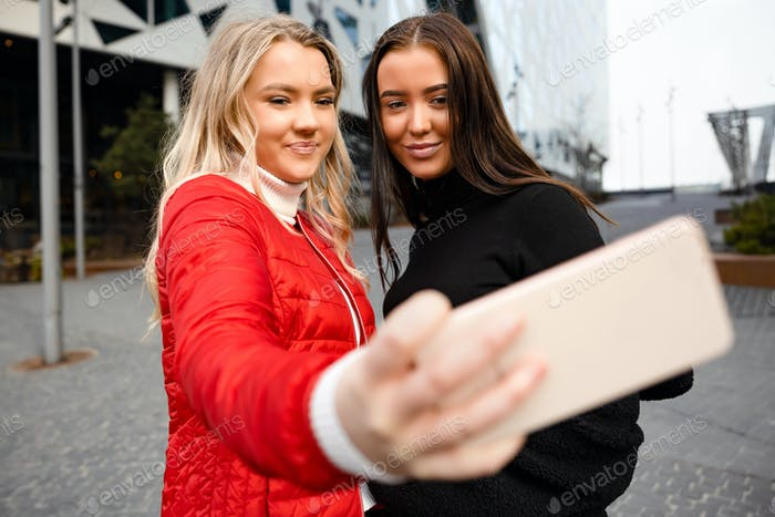 Smiling Beautiful Friends Taking Selfie Through Smartphone In City