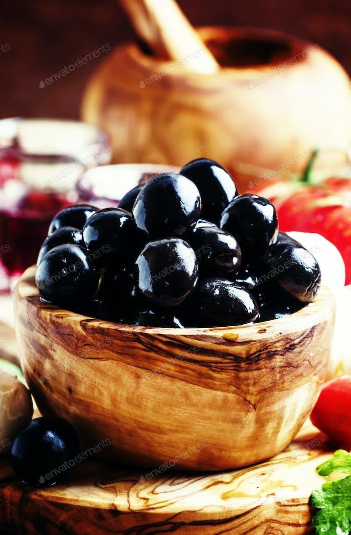 Black olives in a vintage wooden bowl