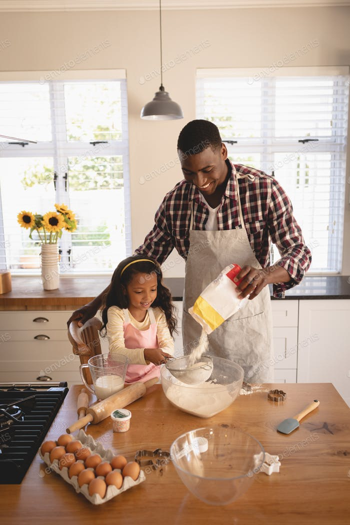 High angle view of African American father and daughter baking cookies in kitchen at home