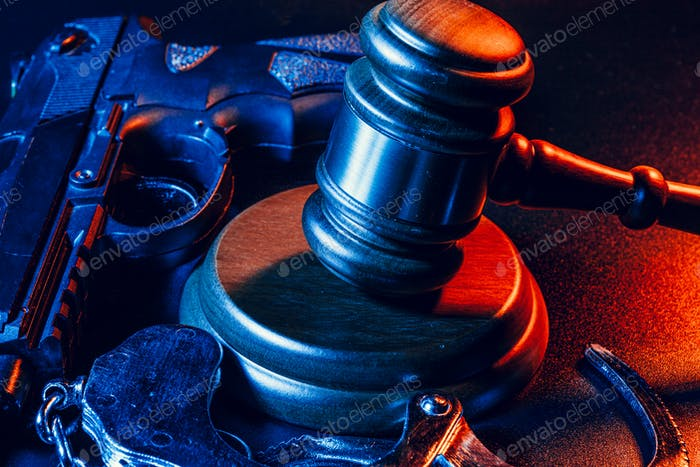 El arma y el maza del juez sobre la mesa. Crimen, robo, concepto de ataque