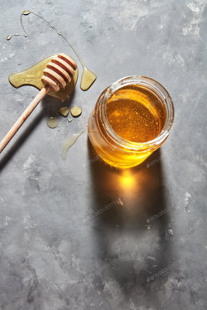 Wooden stick on a spilled honey on the table and glass pot with natural meadow sweet dessert on a