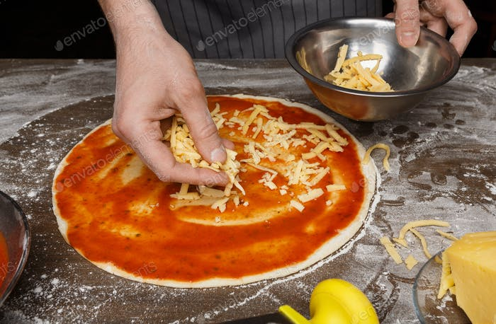 Italian cuisine. Cook adding grated cheese to pizza