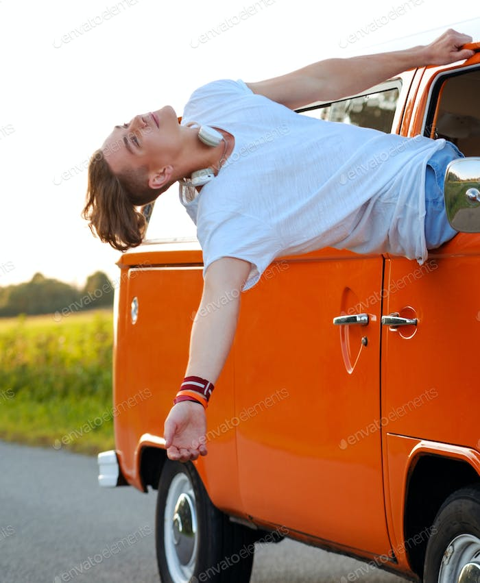 Happy young man in a van on a road trip