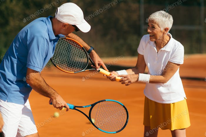 Tennis Instructor with Senior Woman in her 60s Having a Tennis Lesson on Clay Court.
