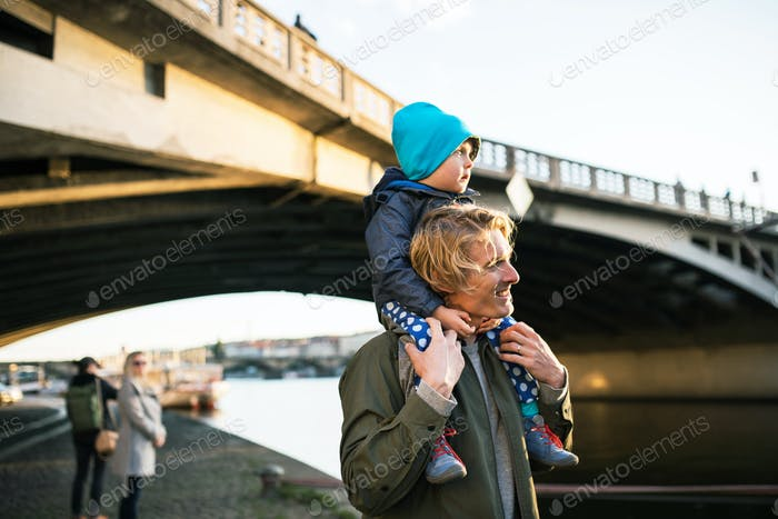 Young father giving their toddler son a piggyback ride outdoors by the river in city.