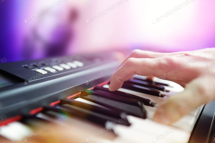 Pianist musician performing live playing keyboard in a band