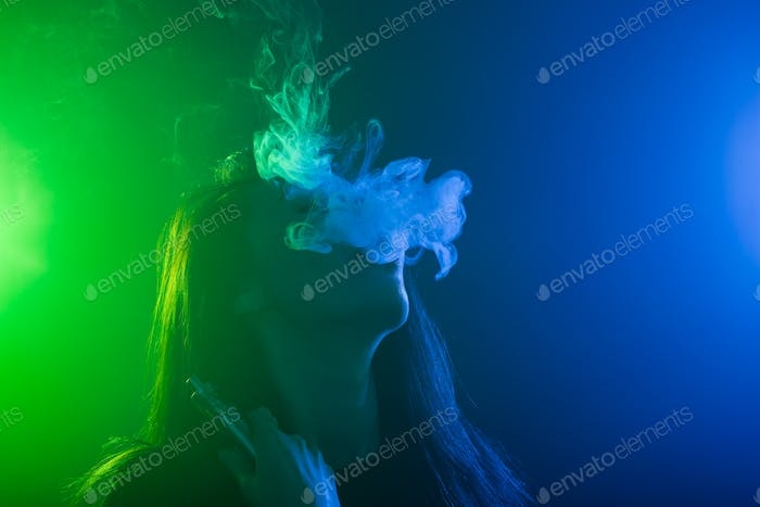 Portrait of young woman in neon blue and green smoke with vape or e-cigarettes