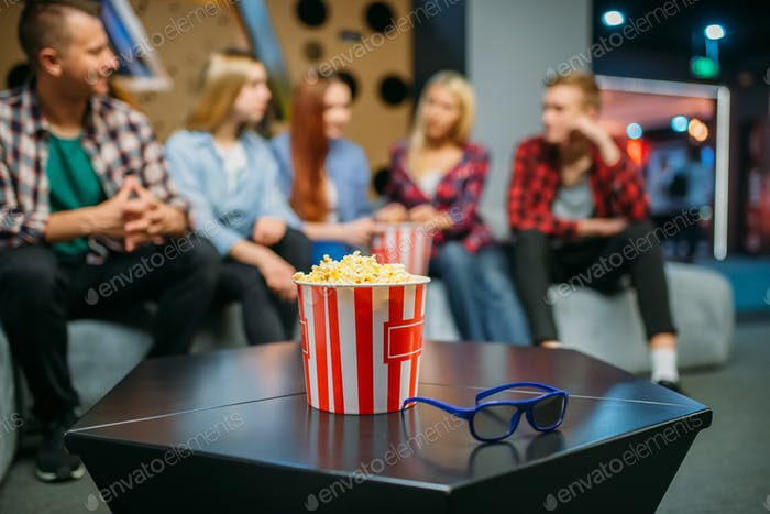Group of teenagers relax on couch in cinema hall