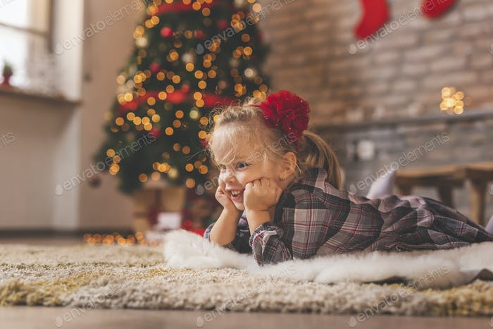Little girl lying by the Christmas tree