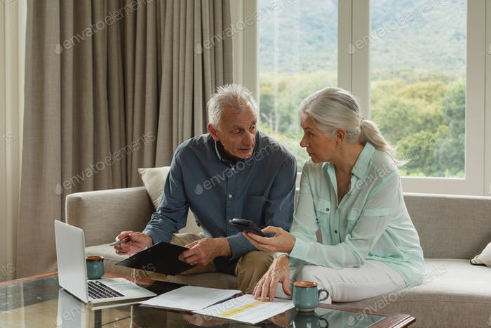 Front view of active senior Caucasian couple calculating bills in living room at home
