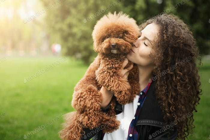 Happy woman with cute curly dog, outdoors portrait