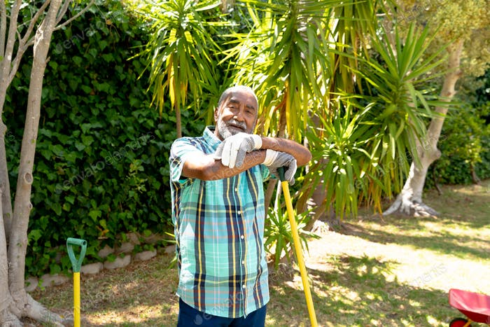 Senior African American man smiling and looking at camera in the garden