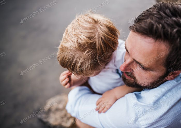 A top view of father with a toddler boy outdoors by the river in summer.