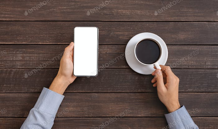 Man holding smartphone with blank screen and drinking coffee