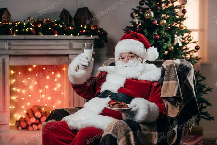 santa claus eating traditional cookies and milk