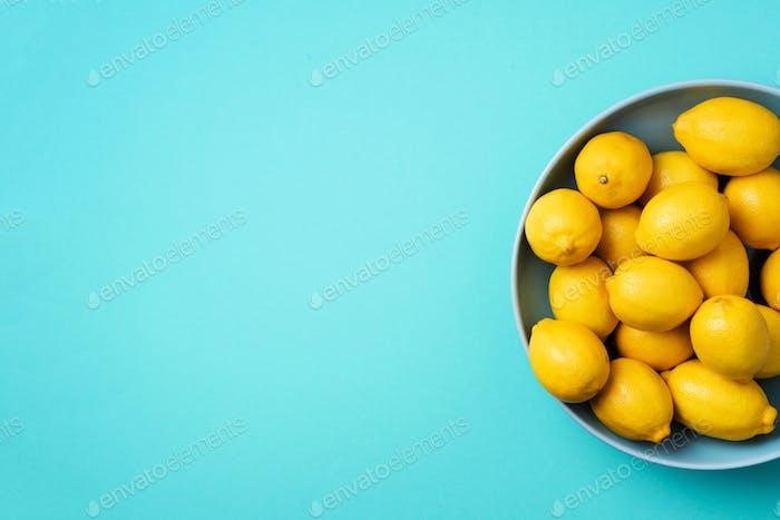 Frische Zitronenfrüchte auf Teller auf blauem Hintergrund.
