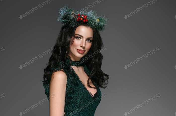 Woman in New Year Decoration beautiful portrait in evening dress over gray background