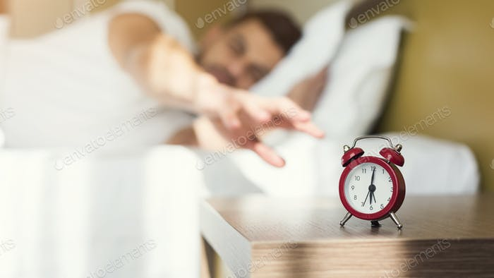 Sleepy guy waking up early after alarm clock signal