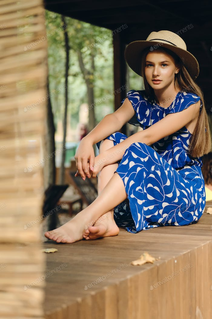 Young beautiful woman in blue dress and hat barefoot thoughtfully looking in camera in city park