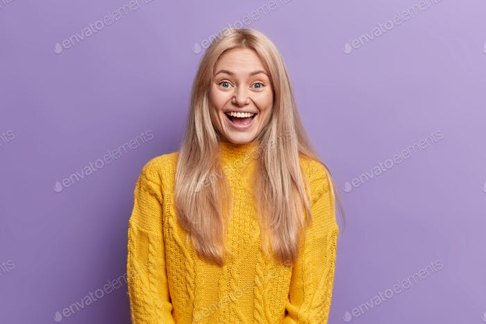 Overjoyed glad blonde European woman with pale face keeps mouth wide opened laughs at something joyf