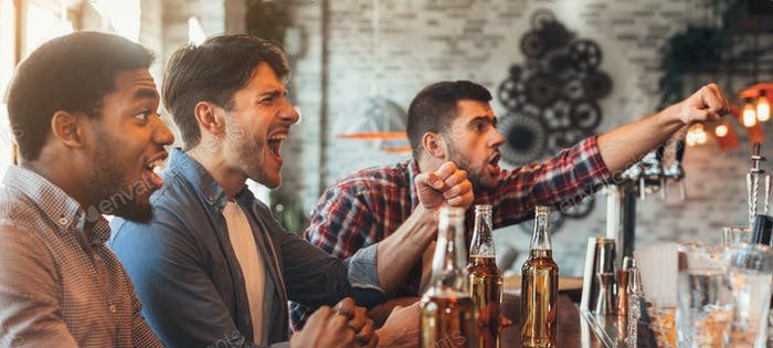 Diverse friends watching football game in bar