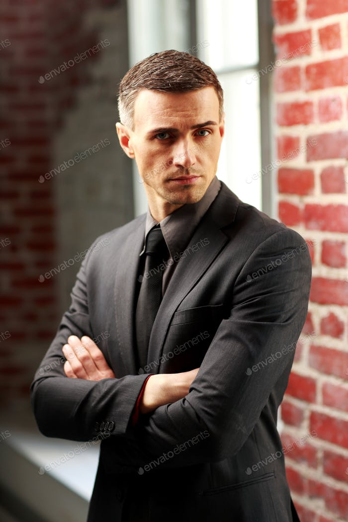 Confident businessman standing with arms folded