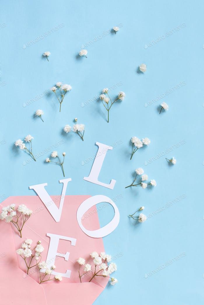 Blumen, rosa Umschlag und Wort Liebe auf hellblauem Hintergrund