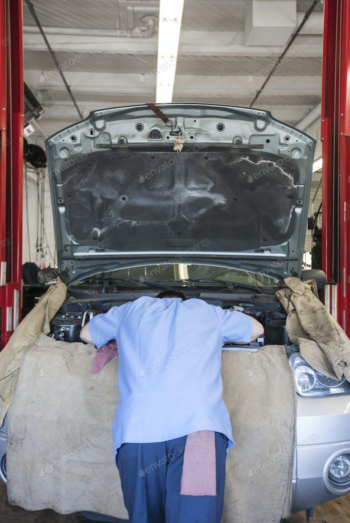 Torso de un mecánico apoyado en el compartimento del motor en un taller de reparación de automóviles