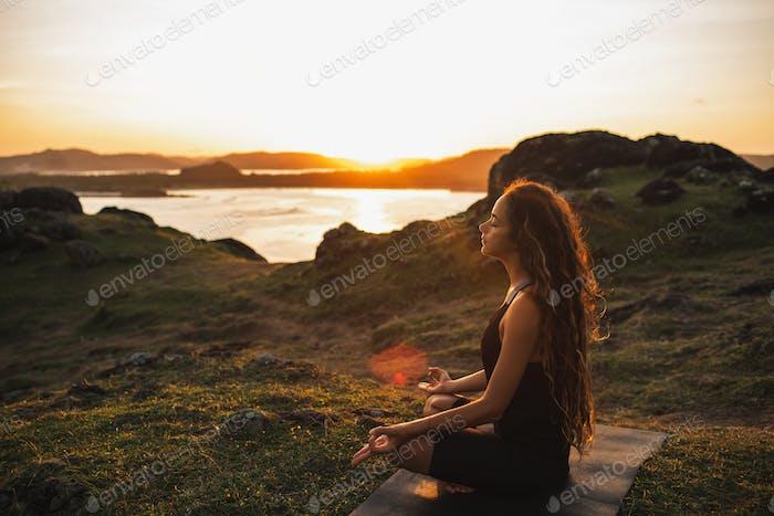 Frau macht Yoga allein bei Sonnenaufgang mit Berg- und Meerblick. Einklang mit der Natur