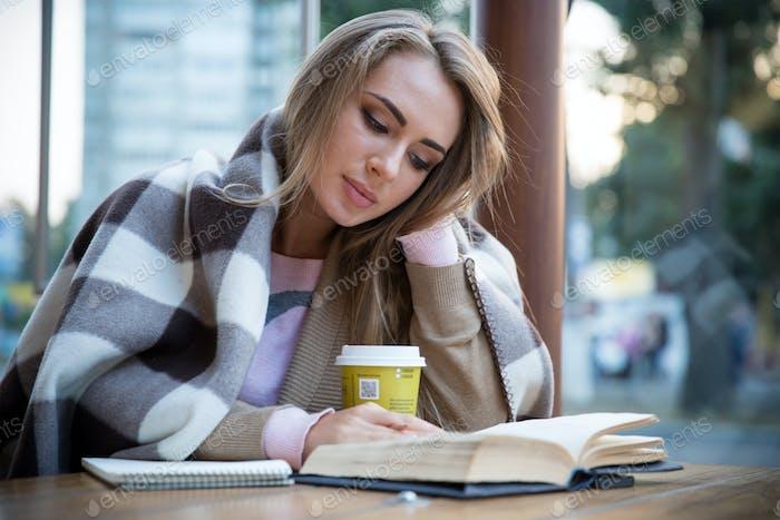 Mädchen lesen Buch im Café