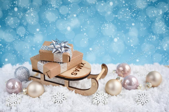 Christmas composition with sleigh, gifts and festive decorations оn the snow