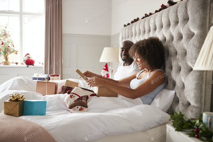 Young adult black woman sitting up in bed on Christmas morning with her partner opening a present