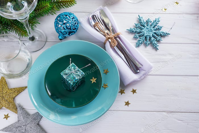 Place table setting for Christmas white table with blue decor elements with green branches Christmas