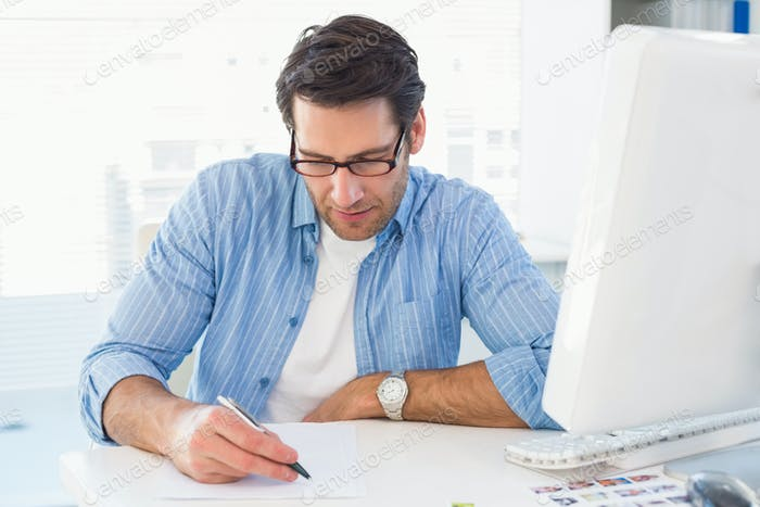 Photo editor writing on a paper in office