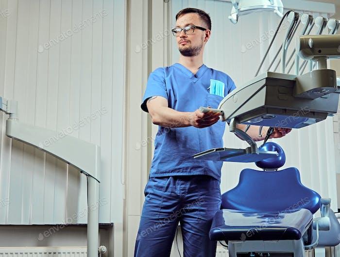 Zahnarzt in einem Raum mit medizinischer Ausrüstung im Hintergrund.