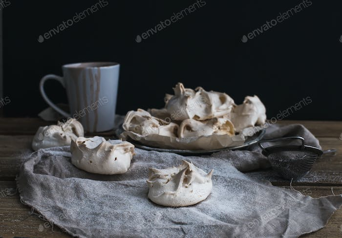 Meringues and mug of hot chocolate on a rustic wooden table. Black background