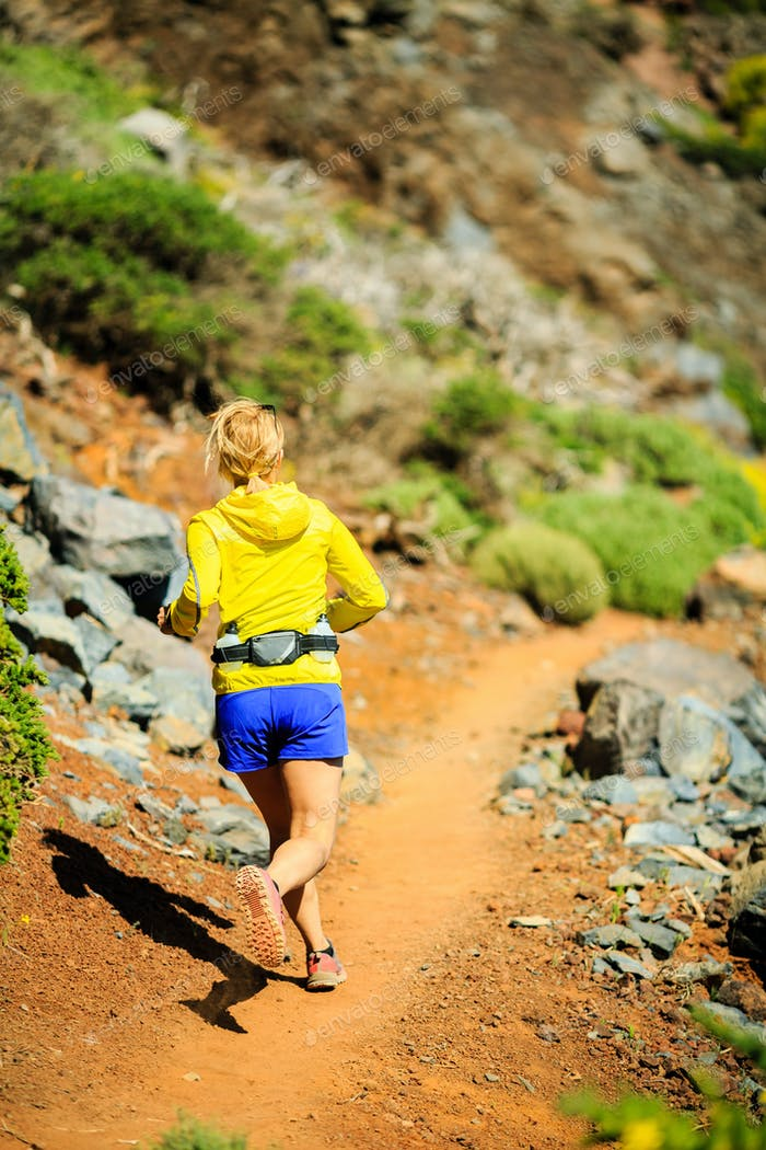 Junge Frau läuft in den Bergen am sonnigen Sommertag