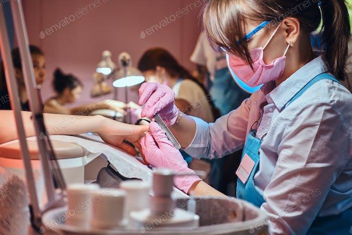 Nail treatment process at busy manicure salon.