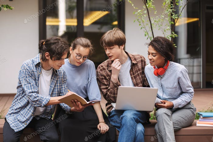 Photo of students sitting on bench with laptop and book