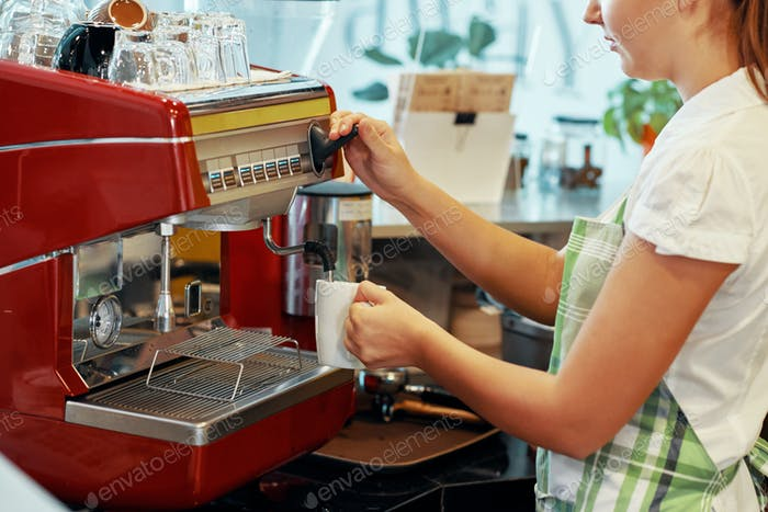 Crop woman brewing coffee with machine