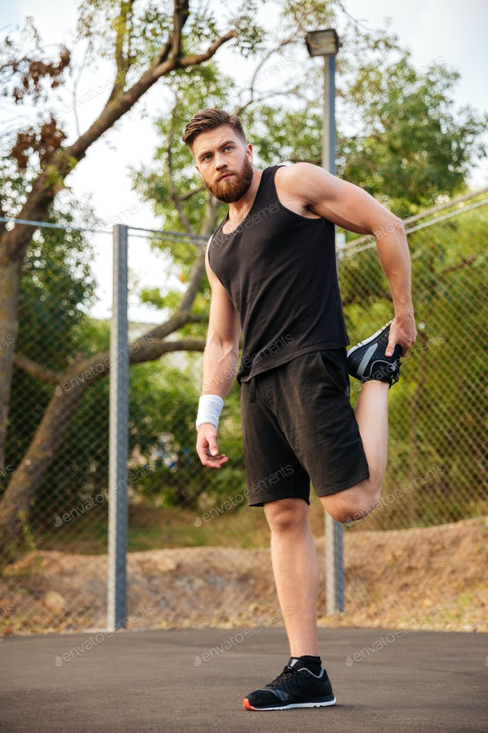 Portrait of a handsome sportsman stretching legs outdoors