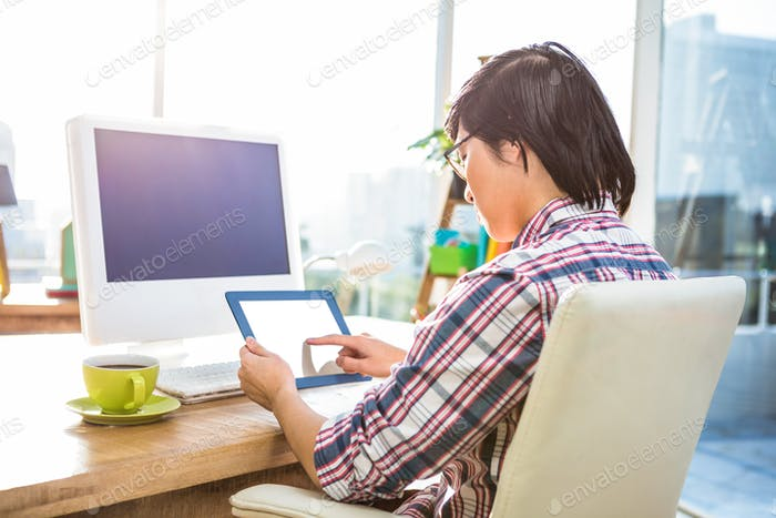 Hipster businessman using tablet in office