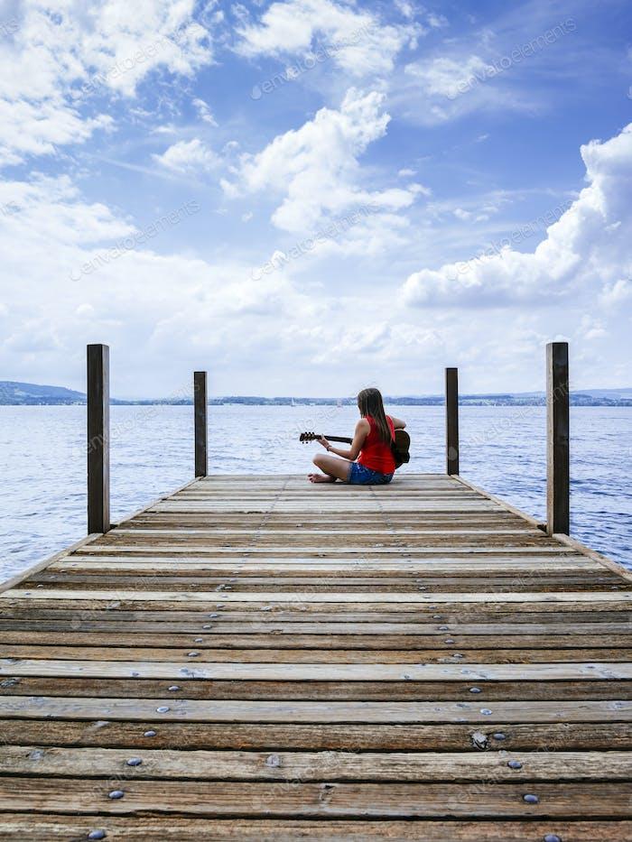 Frau spielt akustische Gitarre am See