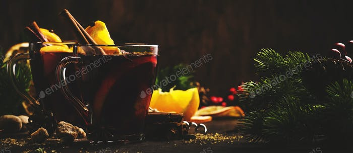 Xmas hot mulled red wine with spices and fruits on wooden rustic table