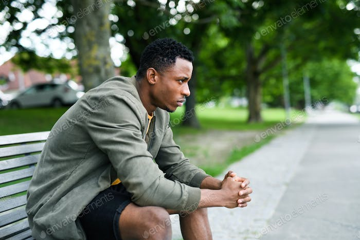 Frustrated young black man sitting on bench outdoors in city, black lives matter concept