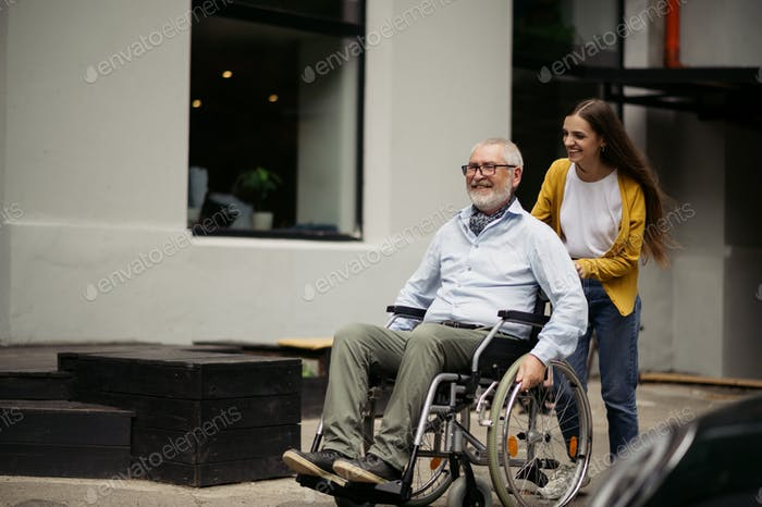Daughter and disabled father go for a walk