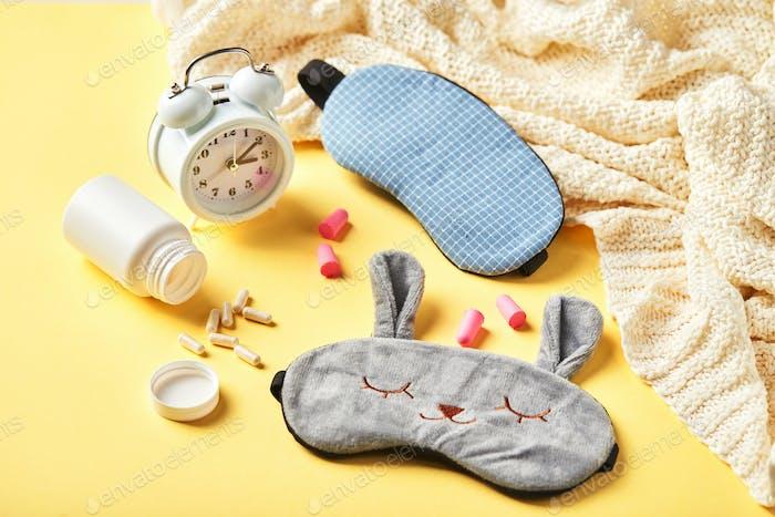Sleeping mask, alarm clock, earplugs and pills on yellow. Healthy night sleep creative concept